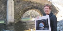 Linda Hale holds the poster of her photograph by the bridge at which she took the photo.